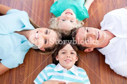 Smiling family lying in circle on the floor