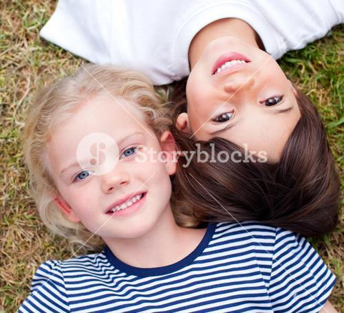 Close up of cute siblings lying on the grass
