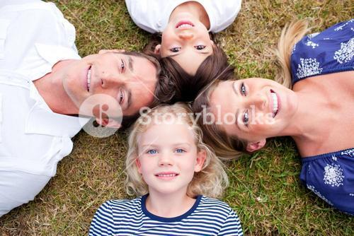 Loving family lying in circle on the grass
