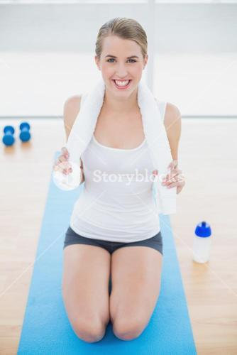 Smiling fit woman on her knees on sport mat posing
