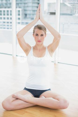 Serious fit woman in lotus position doing yoga session