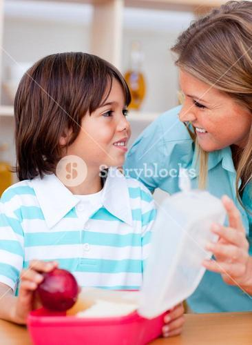 Joyful little boy and his mother preparing his snack