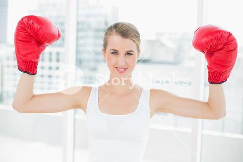 Smiling competitive woman with red boxing gloves cheering up