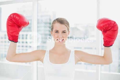 Cheerful competitive woman with red boxing gloves cheering up