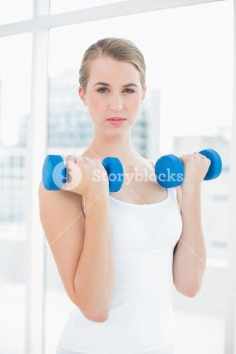 Content fit woman exercising with dumbbells