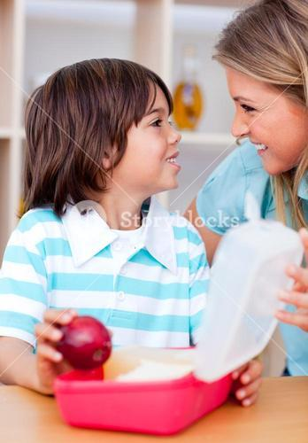 Cute little boy and his mother preparing his snack