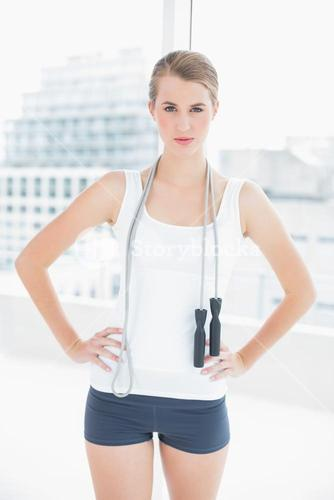Motivated sporty woman holding skipping rope