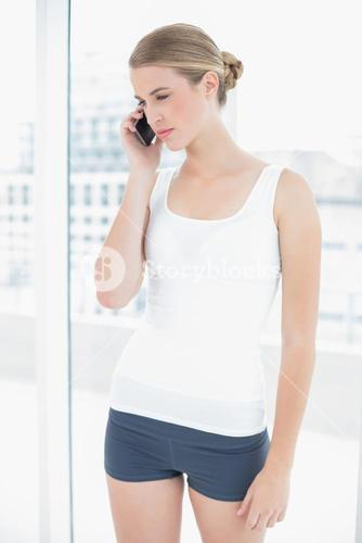 Thinking sporty woman having a phone call