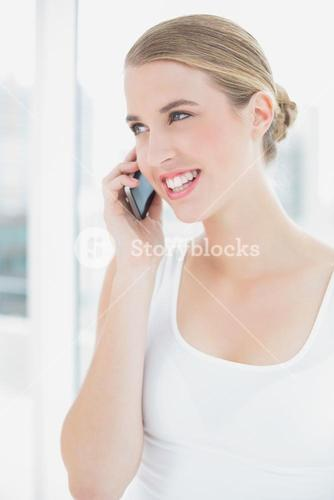 Close up on smiling sporty woman having a phone call