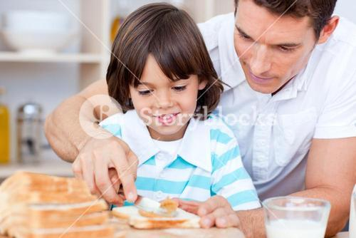 Loving father and his son spreading jam on bread