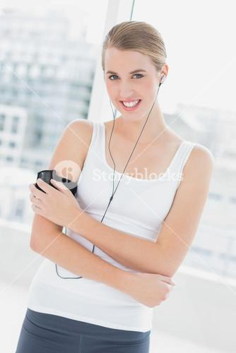 Smiling sporty woman changing song on her mp3