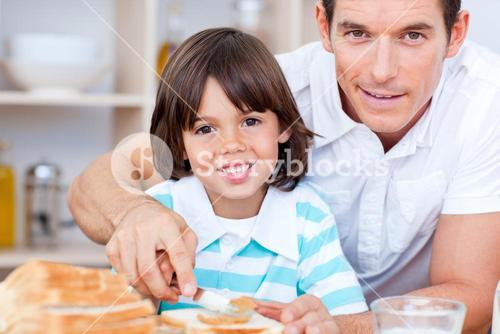 Portrait of a father and his son spreading jam on bread