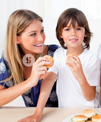 Attractive mother and her son eating burgers