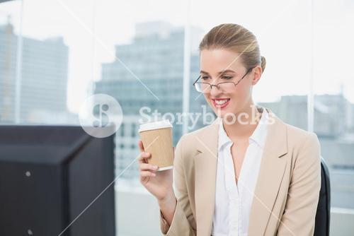 Happy businesswoman with glasses holding coffee