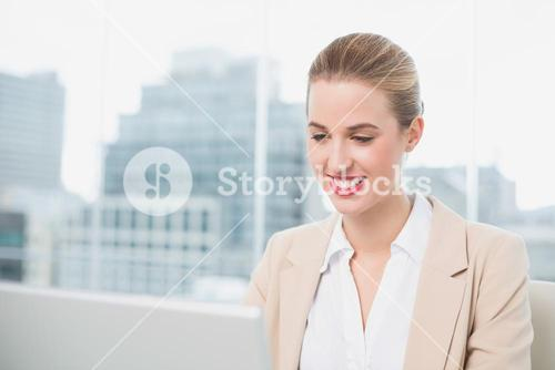 Cheerful gorgeous businesswoman working on her laptop