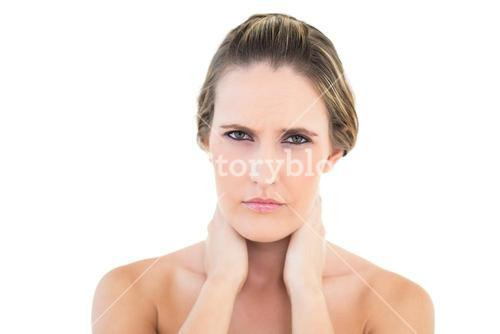 Disgruntled woman looking at camera with a sore neck