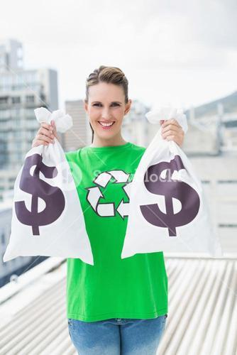 Smiling woman in green recyling tshirt showing money bags