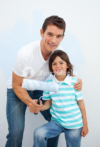 Smiling Father and his boy paiting a room