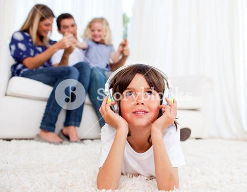 Pensive little boy listening music lying on floor