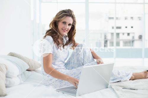 Peaceful woman sitting on cosy bed using laptop