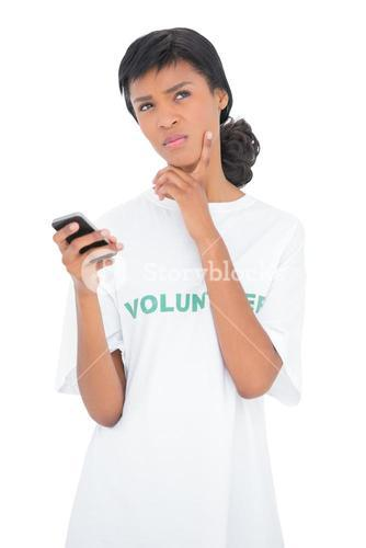 Thoughtful black haired volunteer holding a mobile phone