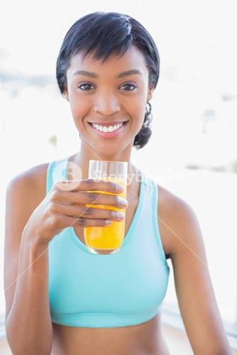 Cheerful fit woman drinking a glass of orange juice