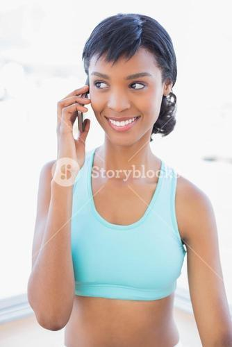 Happy fit woman calling someone with her mobile phone