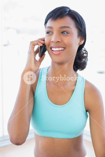 Laughing fit woman calling someone with her mobile phone