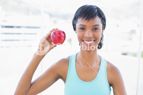 Delighted black haired woman holding an apple