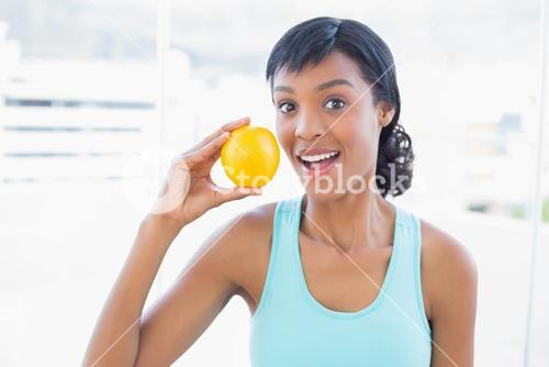Surprised black haired woman holding an orange