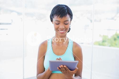 Concentrated black haired woman using a tablet pc