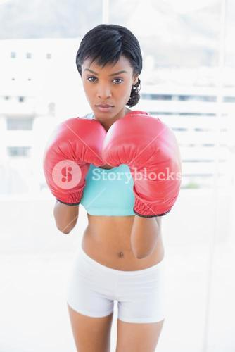 Frowning black haired woman wearing boxing gloves
