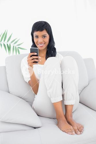 Delighted black haired woman in white clothes typing on her mobile phone