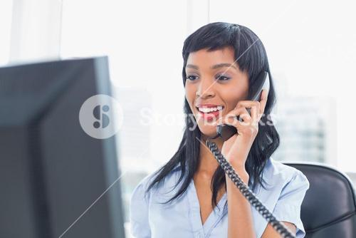 Pleased businesswoman answering the telephone