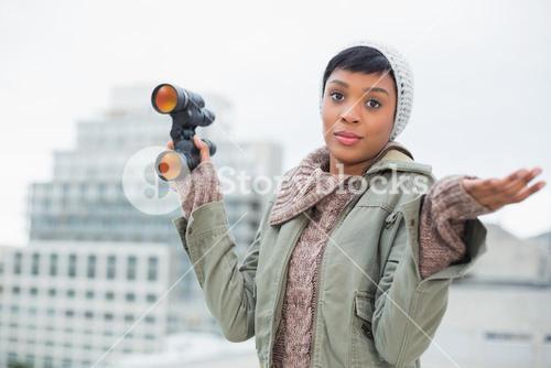 Disappointed young model in winter clothes holding binoculars