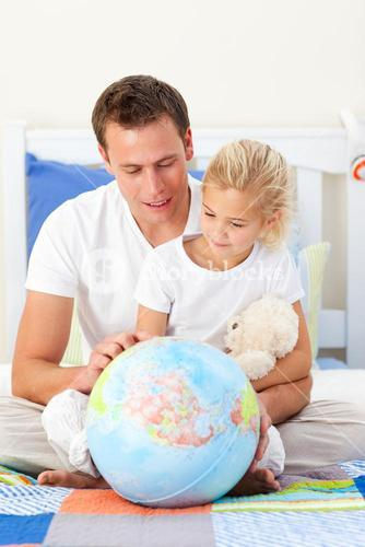 Attentive father and his daughter looking at a terretrial globe