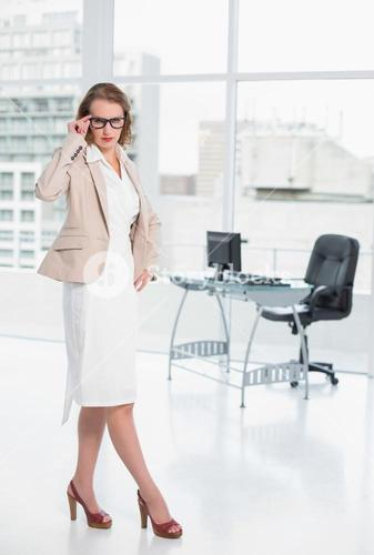 Severe pretty businesswoman looking at camera