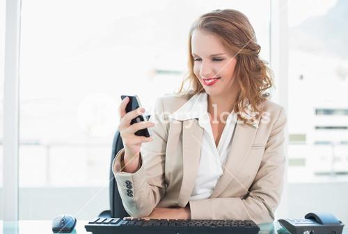 Pleased pretty businesswoman looking at her mobile phone