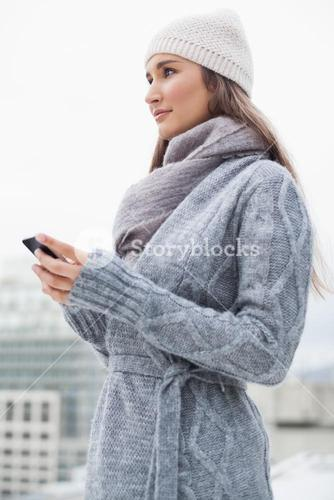 Peaceful woman with winter clothes on text messaging