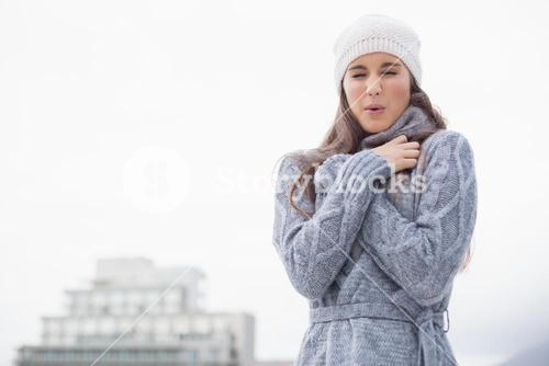 Shivering pretty woman with winter clothes on posing