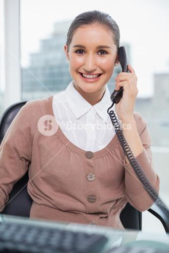 Cheerful businesswoman picking up the phone