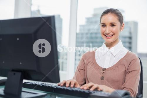 Cheerful gorgeous businesswoman working on her computer
