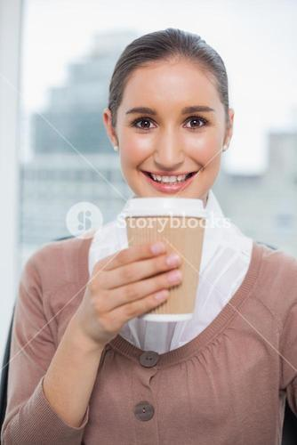 Happy gorgeous businesswoman holding coffee