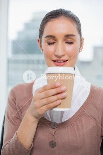 Happy gorgeous businesswoman smelling coffee