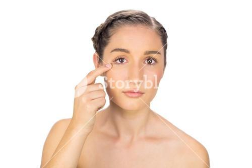 Natural model pointing at her eye