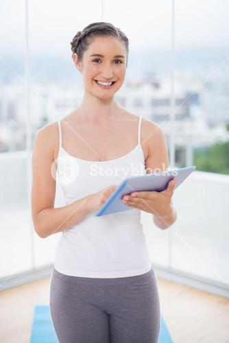 Smiling sporty model using her tablet pc