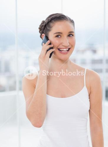Smiling sporty brunette on the phone