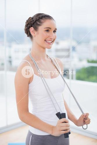 Cheerful sporty brunette holding skipping rope