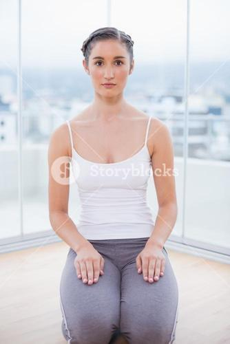 Serious sporty brunette sitting