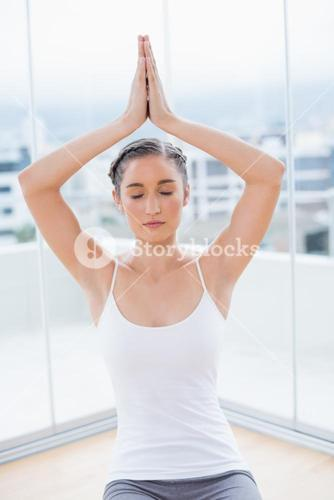 Relaxed sporty brunette sitting in yoga posture